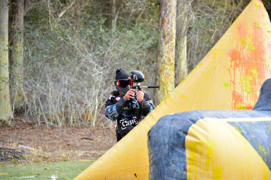 paintball player shooting from behind bunker