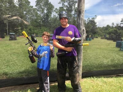 Dad and son playing paintball for birthday party